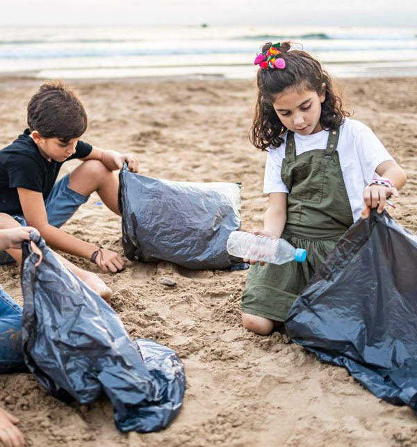 Children cleaning bottled water bottles from beach